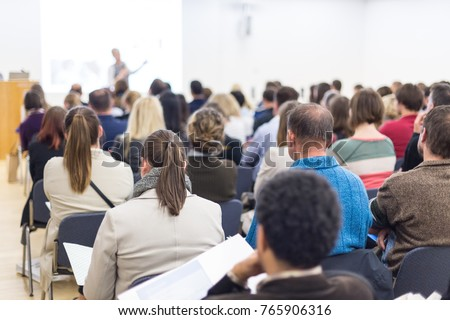 Business and entrepreneurship symposium. Female speaker giving a talk at business meeting. Audience in conference hall. Rear view of unrecognized participant in audience. Copy space on whitescreen. #765906316