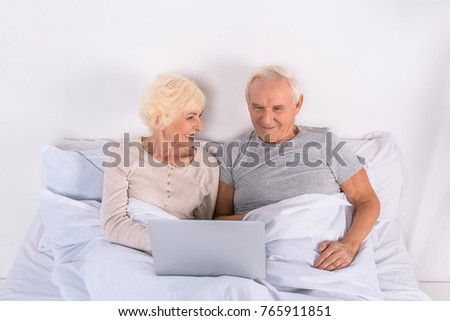 senior couple using laptop while resting in bed at home #765911851