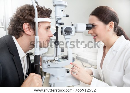A man having an eye test with Slit Lamp / female doctor in ophthalmology clinic doing retina cornea exam diagnostic with vision of patient by modern computer systems - concept health care #765912532