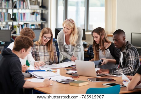 Female Teacher Working With College Students In Library #765915907