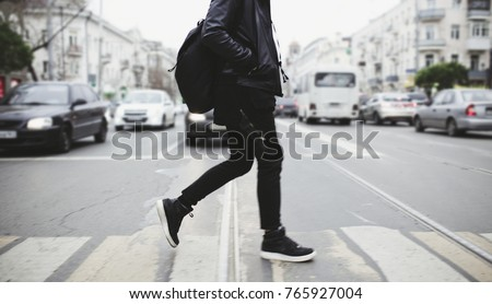 Modern young bearded man in black style clothes is walking at street. Royalty-Free Stock Photo #765927004
