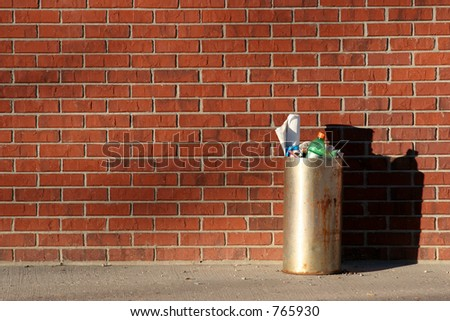 metal trashcan filled and dirty stands against a red brick wall #765930