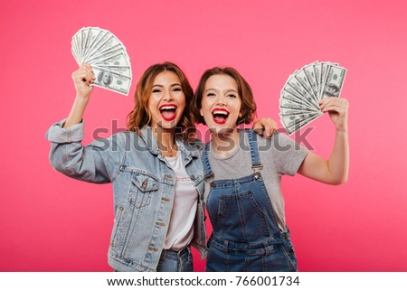 Picture of emotional pretty two women friends holding money isolated over pink background. Looking camera.