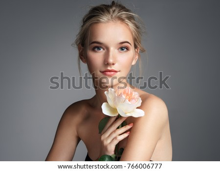 Charming young girl with perfect makeup. Photo of blonde girl with rose on grey background. Skin care concept