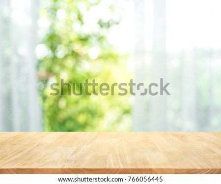 Empty of wood table top on blur of curtain with window view green from tree garden background.For montage product display or design key visual layout #766056445