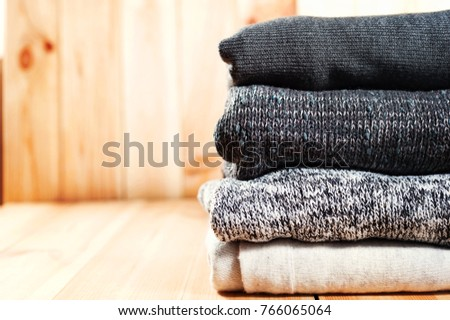 A neat pile of knitted warm blanket or sweaters gray, white on a wooden background. Comfort, warmth and a homely atmosphere in the cold winter. Copyspace #766065064