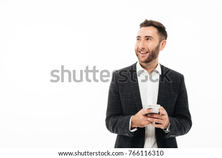 Portrait of a smiling young man holding mobile phone and looking away at copy space isolated over white background #766116310