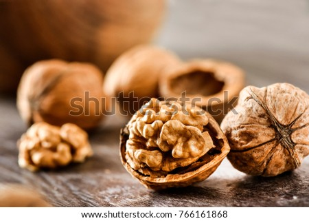 Walnuts kernels on dark desk with color background, Whole walnut in wood vintage bowl. #766161868