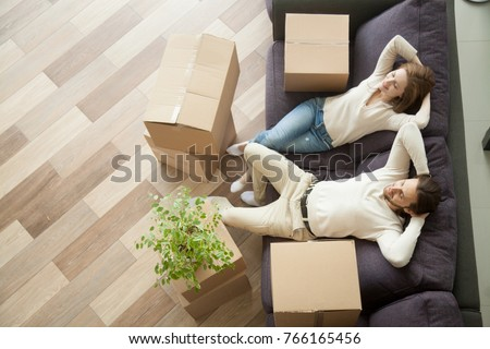 Couple resting on couch after moving in, man and woman relaxing on sofa just moved into apartment with cardboard boxes on floor, happy satisfied homeowners enjoying first day in new home, top view #766165456