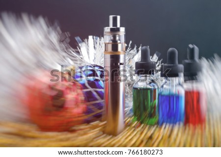 Electronic cigarette with vape liquids within vapor and christmas decorations on black background. Motion blurred #766180273
