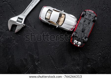 Car repair concept. Wrench near car toys on black background top view copyspace #766266313