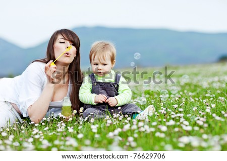 Young mother with child outside on a summer day. #76629706