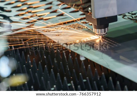 The fiber  laser cutting machine  cutting the sheet metal plate with the sparking light.Hi-technology manufacturing concept. Royalty-Free Stock Photo #766357912