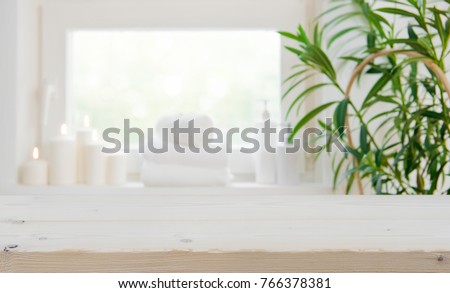 Wooden tabletop with copy space over blurred spa window background #766378381