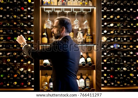 Middle-aged handsome man chooses a bottle of wine #766411297