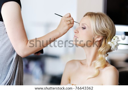 Young beautiful bride applying wedding make-up by make-up artist #76643362