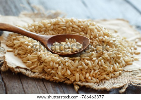 Pile of Brown rice with a wooden spoon close up #766463377