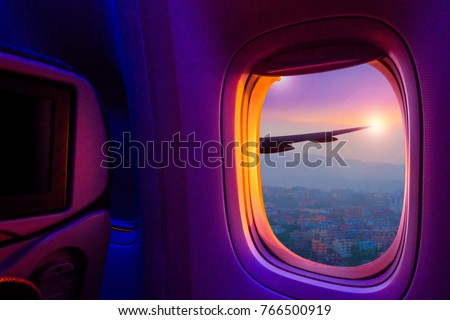 Beautiful scenic city view of sunset through the aircraft window. Image save-path for window of airplane. #766500919
