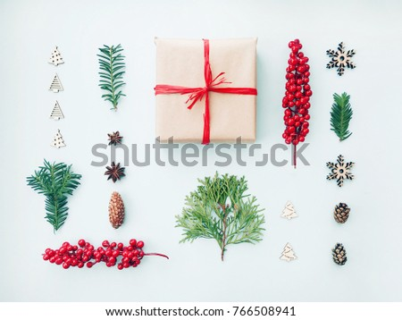 Christmas or new year composition. Christmas gift, pine branches and cones on light background. Flat lay, top view. Layout for Christmas card. #766508941