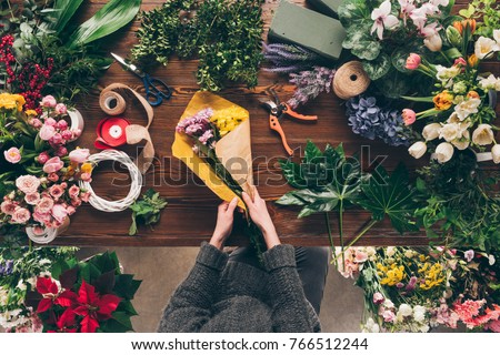 cropped image of florist wrapping bouquet in pack paper in shop #766512244