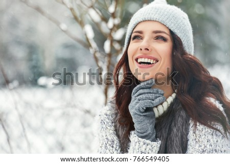 beautiful smiling young woman in wintertime outdoor. Winter concept  #766549405