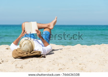 A handsome man relaxing on a book reading on the beach. #766636108