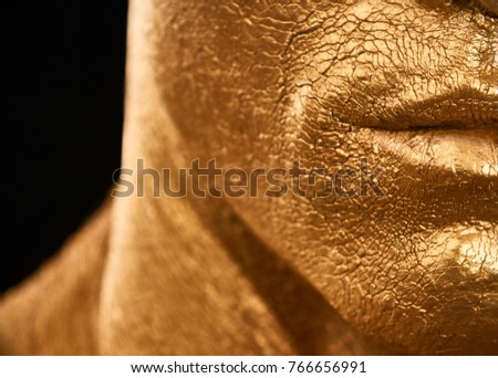 man in gold paint. detail of a man's face courageous lips, neck and chin. A handsome man of athletic build, completely covered in gold paint. Royalty-Free Stock Photo #766656991