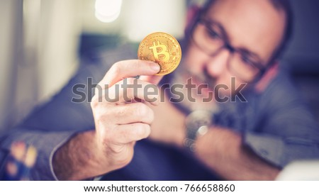 bitcoins - Bitcoin in hand of a casual businessman wondering what the future is #766658860