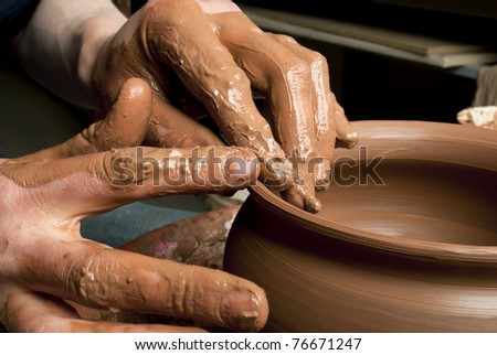 hands of a potter, creating an earthen jar on the circle #76671247
