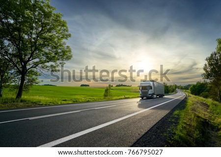 White truck driving on the asphalt road next to the green field in rural landscape at sunset #766795027