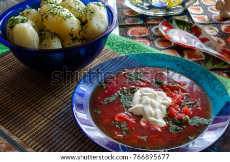 red soup with greens and sour cream on the table #766895677