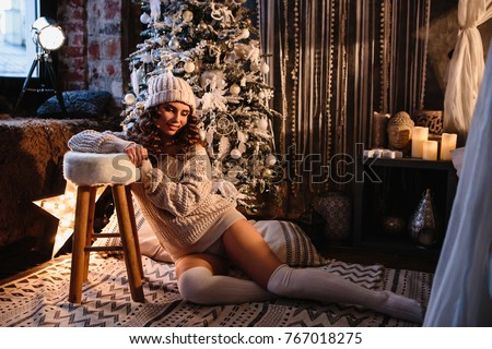 Pretty young woman in a room with christmas decoration. Winter mood, cozy home, scandinavian style #767018275