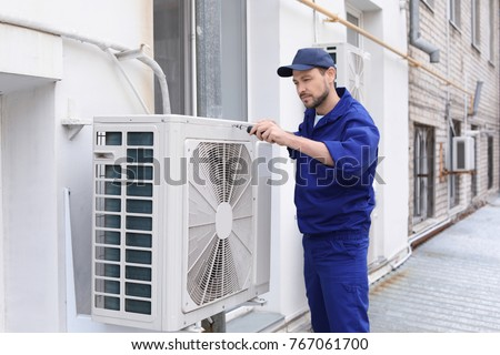 Male technician repairing air conditioner outdoors #767061700