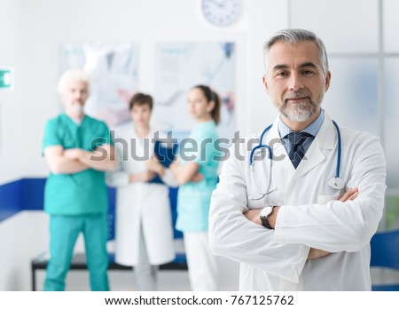 Confident smiling doctor posing and the hospital with arms crossed and medical team working on the background Royalty-Free Stock Photo #767125762