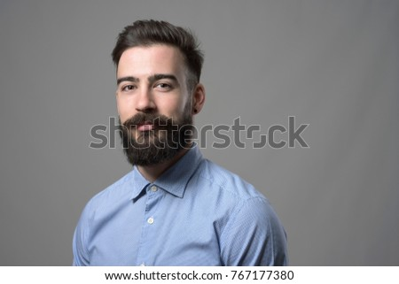 Horizontal portrait of young successful stylish bearded businessman with copyspace against gray studio background. #767177380