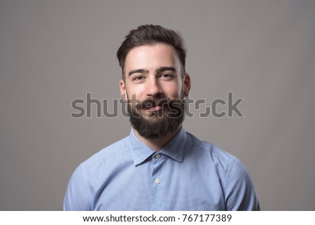 Horizontal  head and shoulder portrait of young bearded business man smiling at camera against gray studio background. #767177389