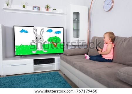 Happy Baby Girl Sitting On Sofa Watching Cartoon On Television