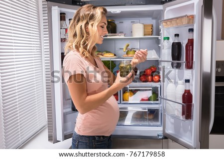 Young Happy Pregnant Woman Eating Pickle From Jar Near Refrigerator #767179858