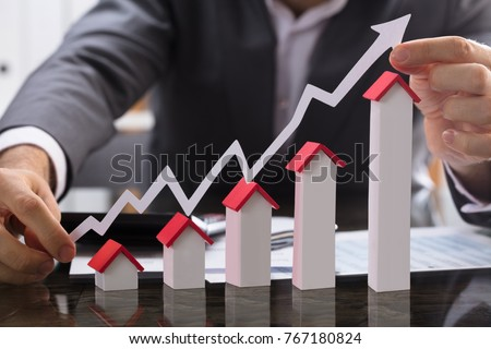 Businessman Holding Paper Graph Over The Increasing House Miniature #767180824
