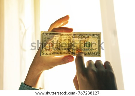 Checking counterfeit money light. 100 dollars against the window in his hand. Check for watermark on new hundred dollar bill. translucence of the American currency.