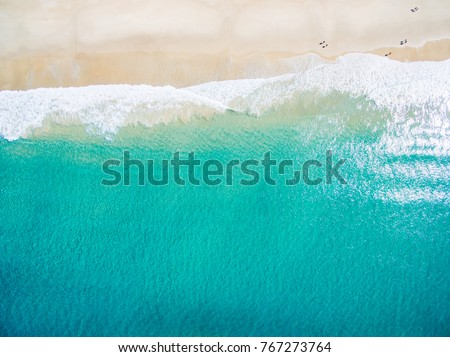 An aerial view of waves crashing on the shore at the beach on a clear day #767273764