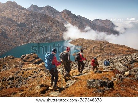 Group of tourists with backpacks descends down mountain trail to lake during a hike in the national park Lantang, Nepal.Beautiful inspirational landscape, trekking and activity. #767348878