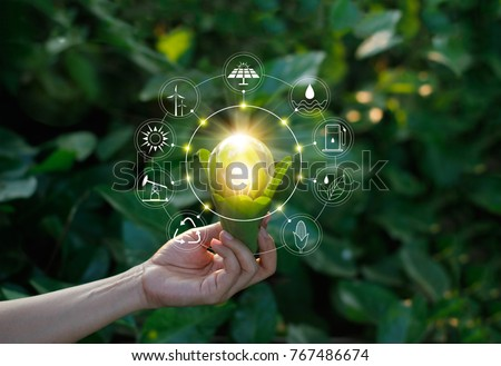 Hand holding light bulb against nature on green leaf with icons energy sources for renewable, sustainable development. Ecology concept. Elements of this image furnished by NASA. Royalty-Free Stock Photo #767486674