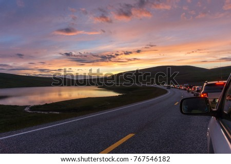 A column of cars on a winding road at sunset, Mageroya island, Norway #767546182