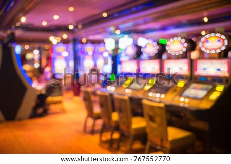 Blurred image of slots machines at the Cruise liner. people playing casino games in yellow tones Royalty-Free Stock Photo #767552770