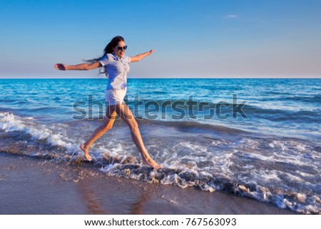 Young beautiful run on a sea or ocean beach in a water splash. Freedom concept #767563093