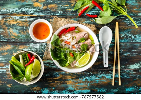 Traditional Vietnamese soup Pho bo with herbs, meat, rice noodles, broth. Pho bo in bowl with chopsticks, spoon. Space for text. Top view. Asian soup Pho bo on wooden table background. Vietnamese soup #767577562