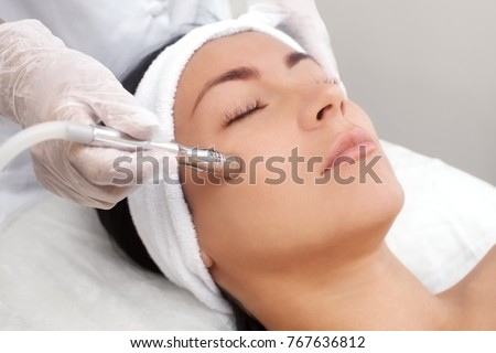 The cosmetologist makes the procedure Microdermabrasion of the facial skin of a beautiful, young woman in a beauty salon.Cosmetology and professional skin care. #767636812