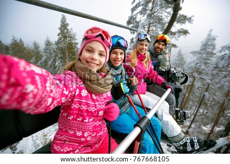 Skiing, ski lift, ski resort - happy smiling family skiers on ski lift making selfie