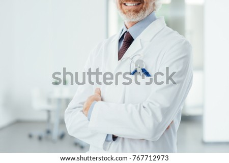 Confident doctor at hospital posing with folded arms and smiling at camera #767712973